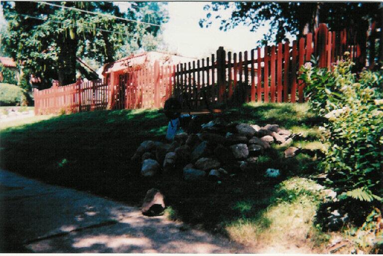 Looking at wall north of driveway, looking north